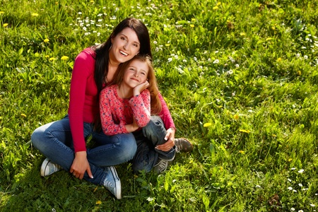 Mother and daughter enjoying summer day sitting on a grass photo