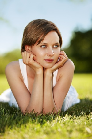 Portrait of attractive woman laying on a grass photo