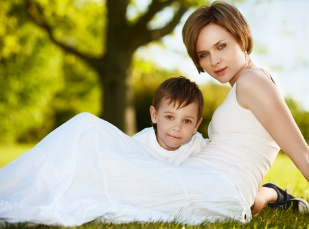 Mother and a little boy enjoying summer outside on a lawn. Focus is on a boy face. photo