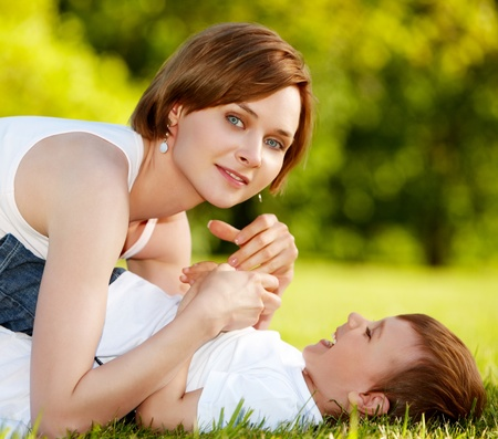 Mother and a little boy enjoying summer outside on a lawn photo