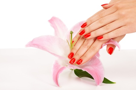 Closeup image of red manicure with a lily flower