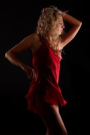 Body of female dancer in red dress in low key photo