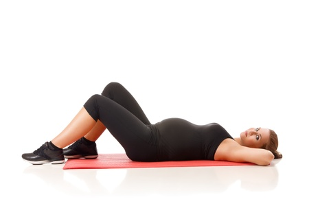 Beautiful pregnant woman doing yoga excercises over isolated white photo