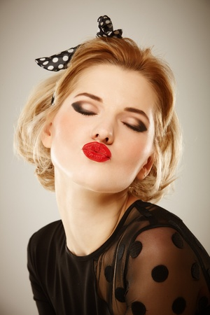 lipstick kiss: Portrait of young woman in retro style wih polka dotted bow Stock Photo