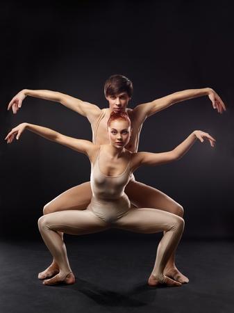 Couple of ballet dancers posing over dark background photo