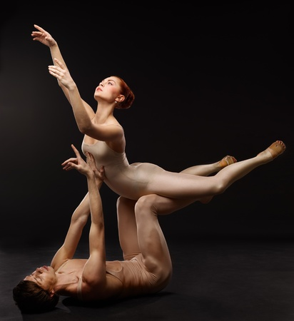 Couple of ballet dancers posing over dark background photo