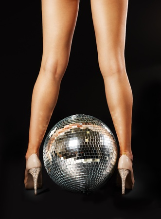 between: Tanned female legs with disco ball over black background