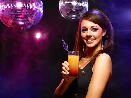 Happy beautiful girl with a drink in nightclub photo