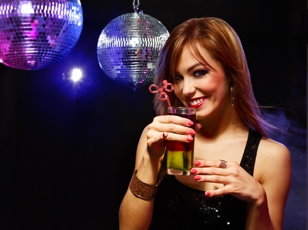 coctail: Happy beautiful girl with a drink in nightclub