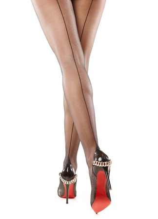 Slim female legs in dark stockings wearing high heels over isolated white Stock Photo - 13288573