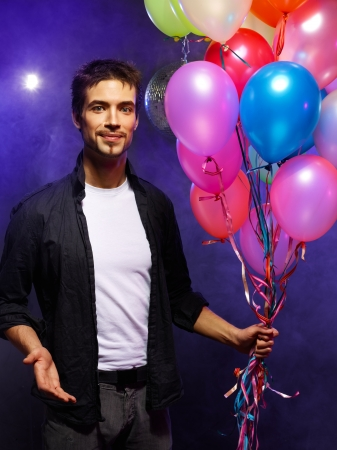 anniversary sexy: Handsome man holding bunch of air balloons Stock Photo