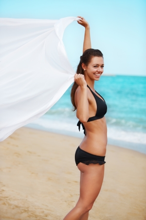 Attractive girl holding pareo on the beach Stock Photo - 14449531