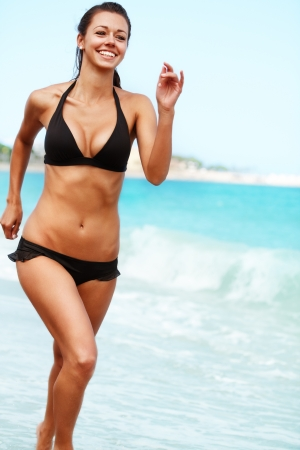 Young attractive woman jogging on the beach Stock Photo