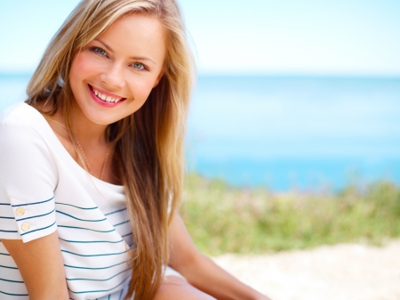 Young attractive woman near the ocean on a summer day photo