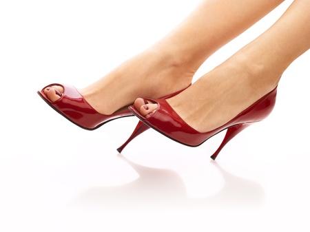 pies sexis: Piernas femeninas en peep toes rojos sobre fondo blanco aisladas Foto de archivo