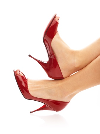 Female legs in red peep toes over isolated white background photo