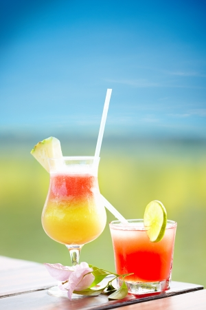 blue hawaiian drink: Glasses with cold fresh drink on a wooden bar over blurred tropical background