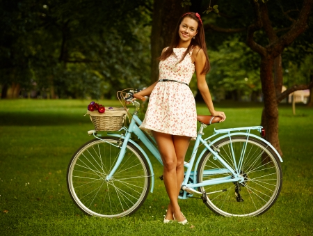 Portrait of pretty pinup girl with blue bycicle in retro style photo
