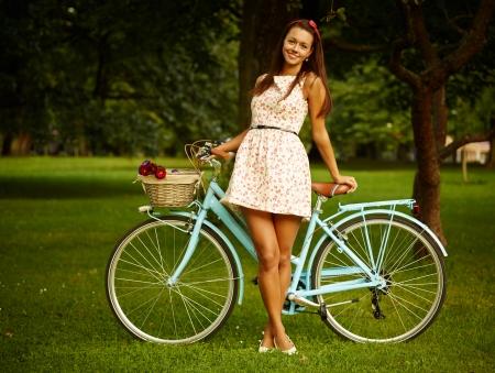piernas mujer: Retrato de la muchacha bonita del pinup con la bicicleta azul en estilo retro