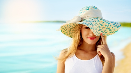 Portrait of beautiful girl on a sunny beach wearing a hat photo