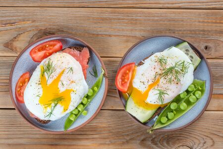 Top view of two Sandwiches with a poached egg and peas and tomato on a plate on wooden background Stockfoto