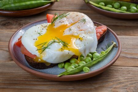 Sandwich with a poached egg and peas and tomato on a plate on wooden background. Selective focus. Stockfoto