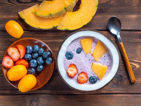 Top view of blueberry smoothie in a coconut bowl with strawberries and melon and kumquat on a rustic wooden background.