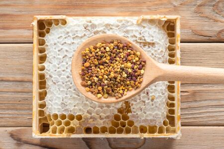 The wooden spoon of bee pollen with honeycombs on wooden background Stock Photo