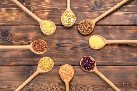View of different types of grains and cereals in wooden spoons on wooden background