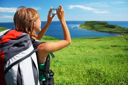 nature picture: Young woman with backpack taking photo of a great landscape Stock Photo