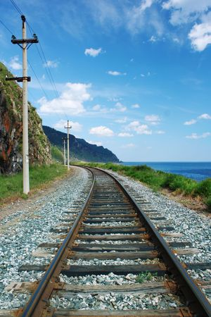 Railroad between mountains and lake photo