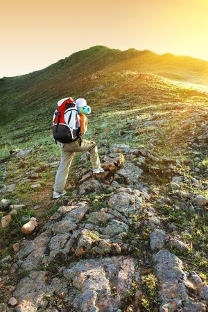 Young woman with backpack walking to the top of hill Stock Photo - 5596834