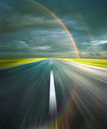 虹が反射虹とアスファルトの道路と嵐の雲