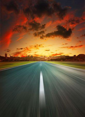 high desert: Asphalt road to city under dramatic sunset