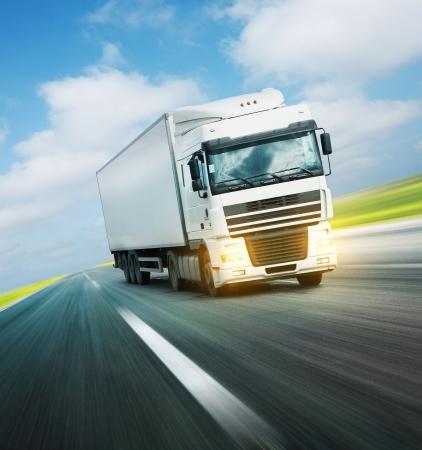 transporte de mercancia: Camioneta blanca en la carretera de asfalto bajo el cielo azul con nubes