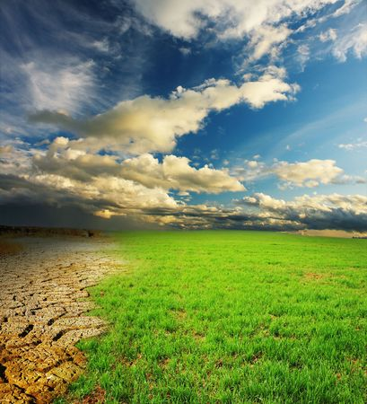 warming: Green grass and cracked desert land over dramatic clouds Stock Photo