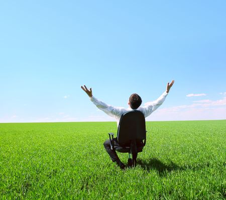 Young businessman sitting in chair on green field photo