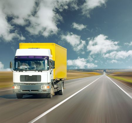 Yellow truck on road under blue sky photo