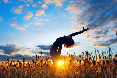 inclination: Young woman under sunset light in meadow with herbs