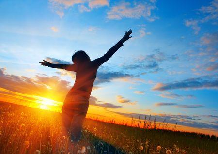 夕日の光の下で牧草地の若い女性 写真素材