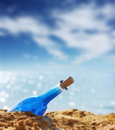 Blue glass bottle in sand and airy clouds like genie photo