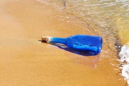 Blue bottle with cork on beach photo