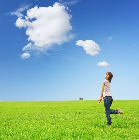 blue sky thinking: Playfull young woman on green grass with fairy clouds Stock Photo