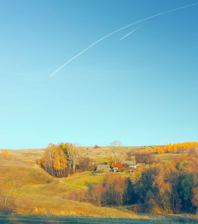 Village with autumn trees and blue sky with plane traces photo