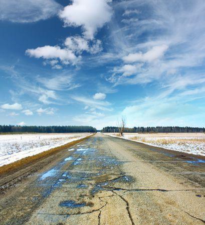 mud and snow: Wet spring asphalt road