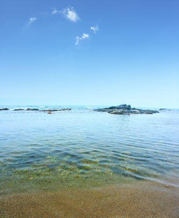 Blue transparent sea and sky with rare clouds photo