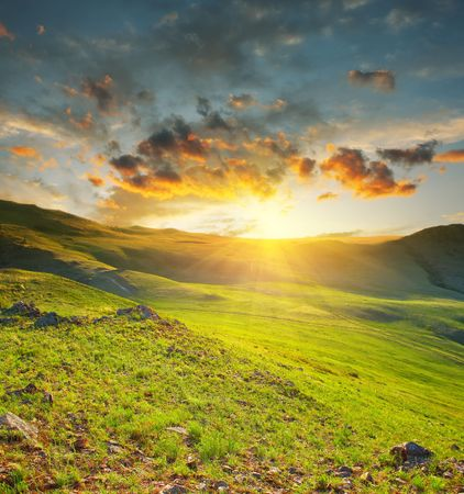 Sunset over green meadow in mountains photo
