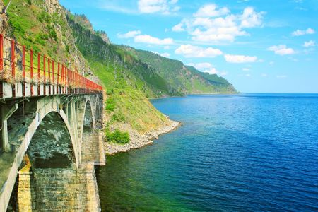 Old bridge between lake with blue clear water and mountains Stock Photo - 5776955