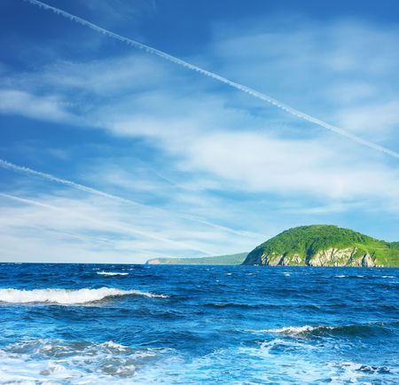 Sea with waves and green island photo