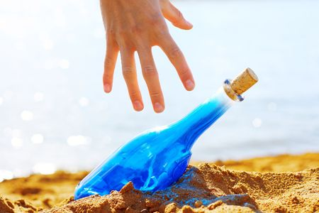 Hand and blue glass bottle in sand photo